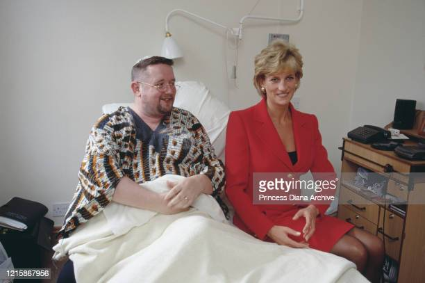 British royal Diana Princess of Wales wearing a red twopiece suit by Catherine Walker sits with a patient during a visit to London Lighthouse a...