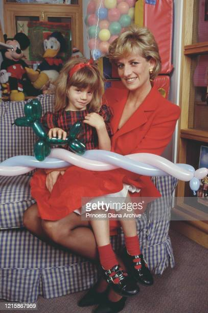 British royal Diana Princess of Wales wearing a red twopiece suit by Catherine Walker with a child holding a balloon dog during a visit to London...