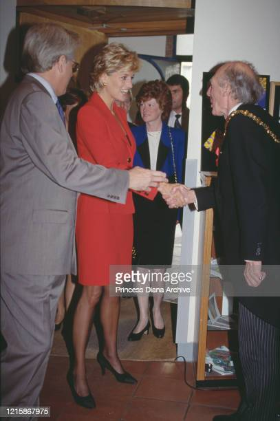 British royal Diana Princess of Wales wearing a red twopiece suit by Catherine Walker meeting dignitaries during a visit to London Lighthouse a...