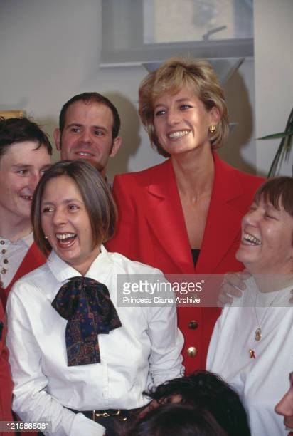 British royal Diana Princess of Wales wearing a red twopiece suit by Catherine Walker with staff during a visit to London Lighthouse a centre for...
