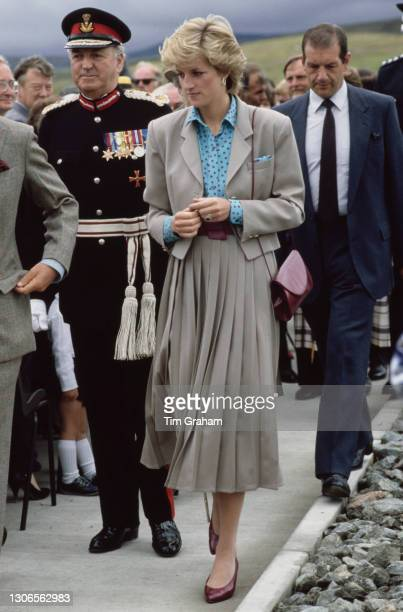 British Royal Diana, Princess of Wales, wearing a turquoise and red polka dot shirt with a beige, pleated skirt suit, with unspecified dignitaries...