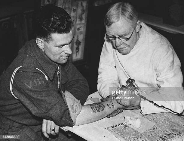 A British Royal Marine has his regimental number tattooed onto his wrist by George Burchett of London