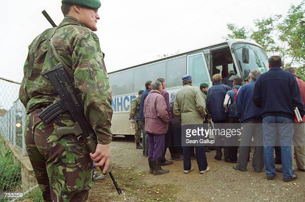 A British Royal Marine with the KFOR stands guard as ethnic Serbs board a UNHCR bus October 20 2000 in Gornje Brnjica a Serb village just north of...
