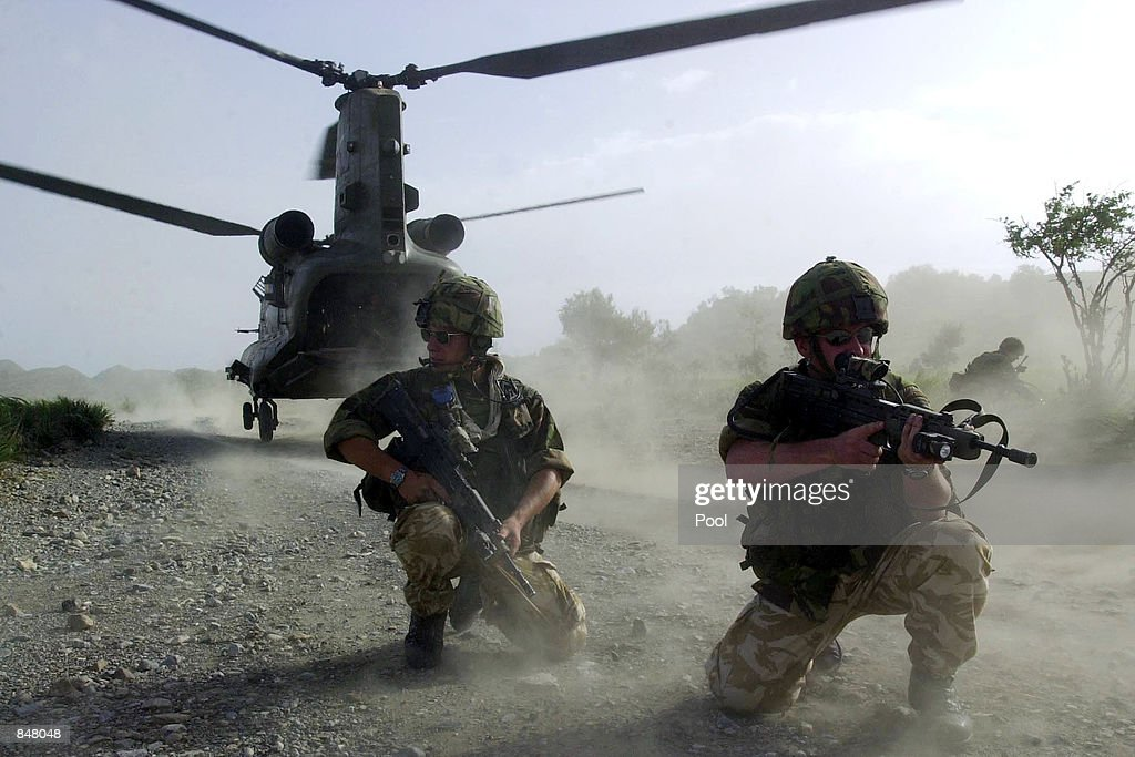 British Royal Marines of 45 Commando take up defensive positions as they disembark a chinook helicopter while conducting vehicle stops and searches on June 26, 2002. British Forces conducted the searches of vehicles near the Afghanistan-Pakistan border as part of the ongoing Operation Buzzard.