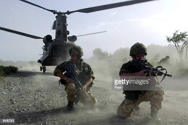 British Royal Marines of 45 Commando take up defensive positions as they disembark a chinook helicopter while conducting vehicle stops and searches...