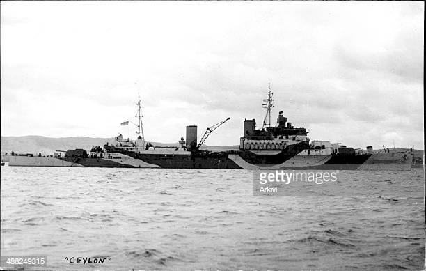 British Royal Navy Battleship HMS Ceylon, in dazzle camouflage anchoring in an undisclosed naval port, date not given.