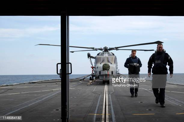 British Royal Navy members maintain a helicopter on board the HMS Montrose frigate during a joint exercise with Japanese Maritime Self-Defense Force...