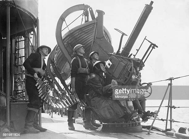 British Royal Navy sailors aboard a destroyer on escort duty fire warning shots to an unidentified aircraft by a 2 pounder pom pom gun on deck May...