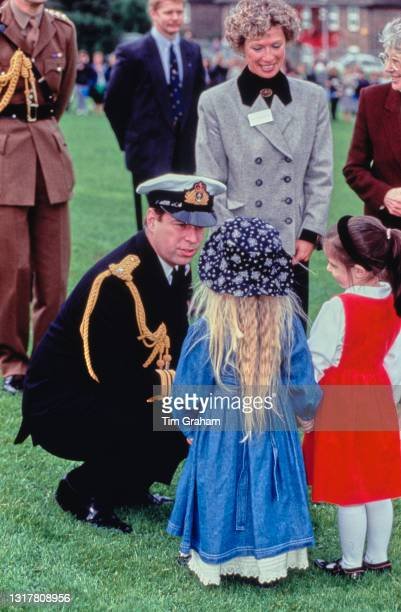 British Royal Prince Andrew, dressed in naval uniform, crouches to speak to two young girls during a visit to the Moulsecoomb Infant & Nursery School...