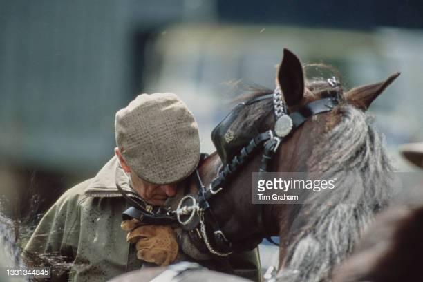 British Royal Prince Philip, Duke of Edinburgh , wearing a flat cap and a waxed jacket, nuzzles a horse at the Royal Windsor Horse Show, held at...