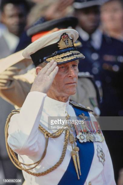 British Royal Prince Philip, Duke of Edinburgh wearing a white ceremonial naval uniform salutes during a wreath-laying at the National Mausoleum in...