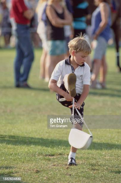 British Royal Prince William, his right leg raised as he stands with his mother's handbag, attends the Cartier International Polo Day, held at the...