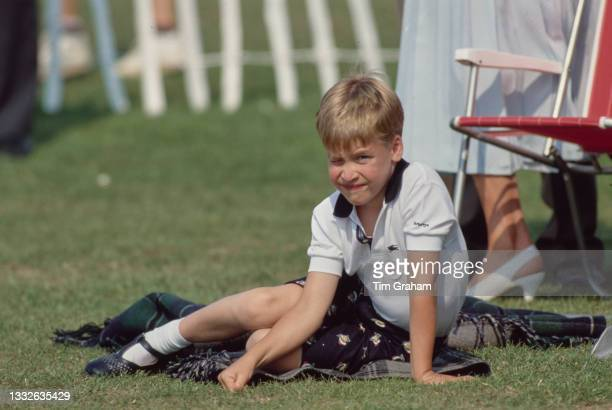 British Royal Prince William sits on the ground beside a red lawn chair during the Cartier International Polo Day, held at the Guards Polo Club,...