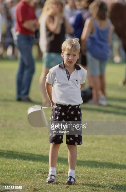 British Royal Prince William, standing with his mother's handbag behind his back, attends the Cartier International Polo Day, held at the Guards Polo...