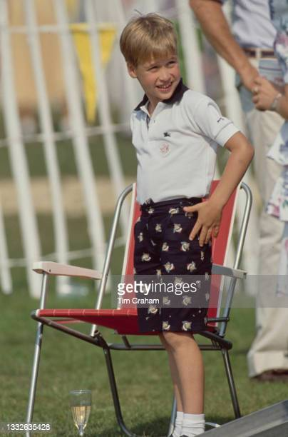 British Royal Prince William stands beside a red lawn chair during the Cartier International Polo Day, held at the Guards Polo Club, Smiths Lawn,...