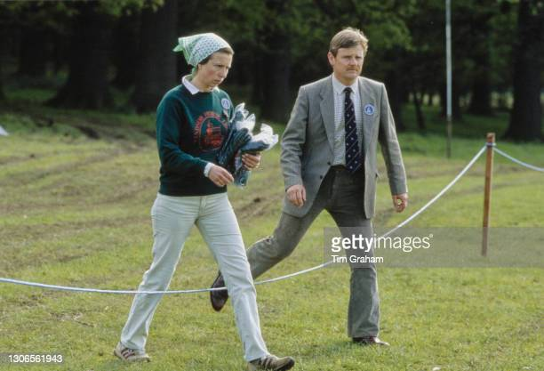 British Royal Princess Anne, Princess Royal, wearing a Windsor Horse Trials sweatshirt, carrying items in her arm while walking with an unspecified...