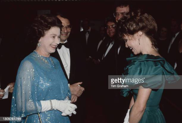 British Royal Queen Elizabeth II, wearing a blue outfit with white evening gloves, speaks with American actress Sally Field meets at the premiere of...