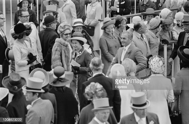 British royal Queen Elizabeth II with Iranian royal Mohammad Reza Pahlavi , Shah of Iran, walk among the racegoers attending the Royal Ascot race...