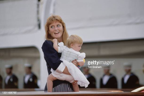 British Royal Sarah, Duchess of York, wearing a dark blue blouse with white collar and cuffs, with her daughter, Princess Beatrice, as she boards HMY...