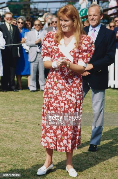 British Royal Sarah, Duchess Of York, wearing a red-and-white dress, attend a polo match being played to benefit handicapped children, held at the...