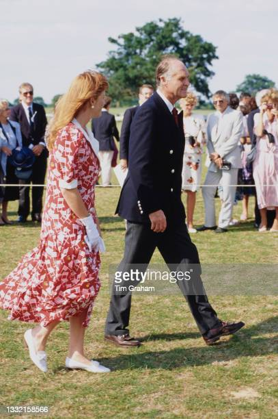 British Royal Sarah, Duchess Of York, wearing a red-and-white dress, and her father Major Ronald Ferguson attend a polo match being played to benefit...