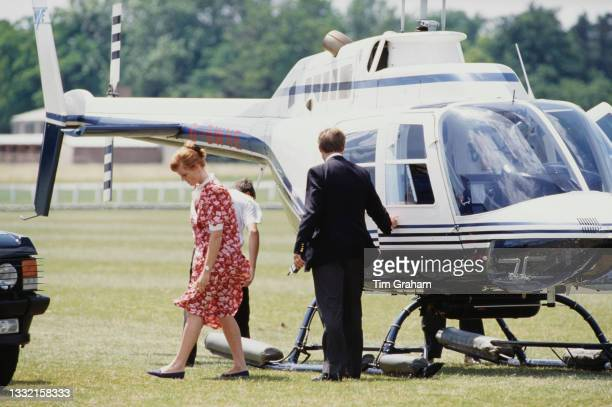 British Royal Sarah, Duchess Of York, wearing a red-and-white dress, following her arrival in a Bell 206 helicopter to attend a polo match being...