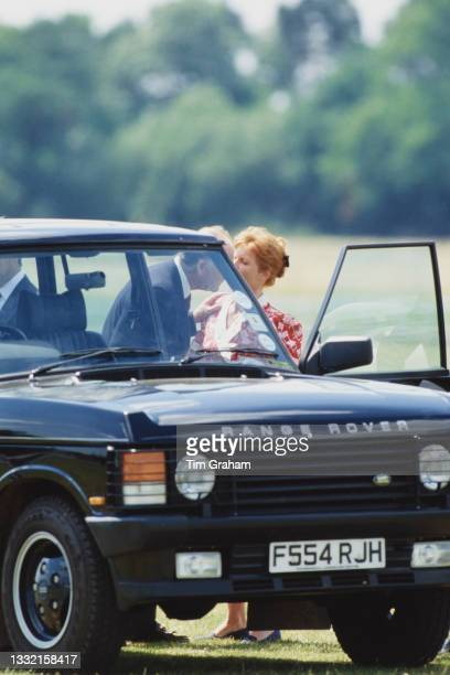 British Royal Sarah, Duchess Of York, wearing a red-and-white dress, with an unspecified man beside a Range Rover Classic as she attends a polo match...