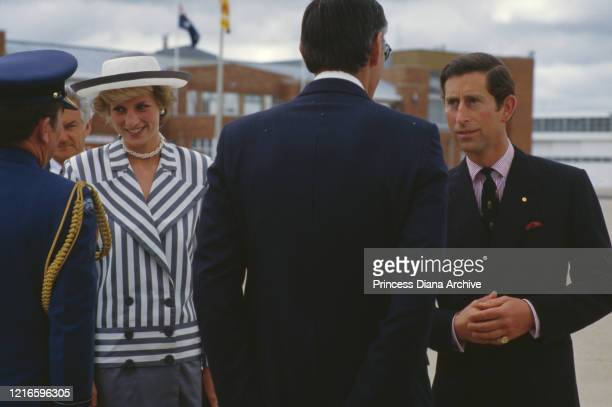 British royals Diana Princess of Wales wearing a blueandwhite striped jacket a dark blue skirt with a white hat with blue trim and Prince Charles...