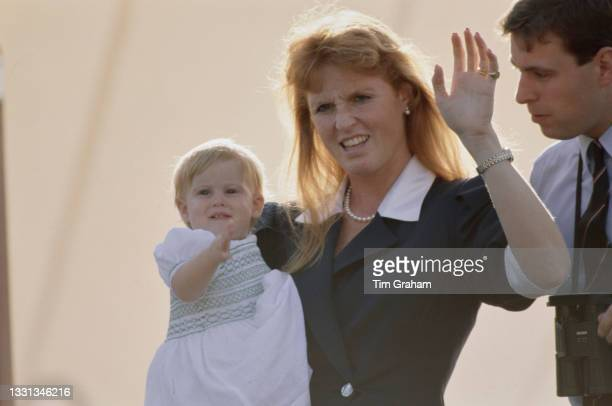British Royals Prince Andrew, Duke of York, and his wife Sarah, Duchess of York, wearing a dark blue blouse with white collar and cuffs, with their...