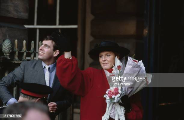 British Royals Prince Andrew, Duke of York and Sarah, Duchess of York, who wears a red coat, black gloves and a black hat, during an official visit...