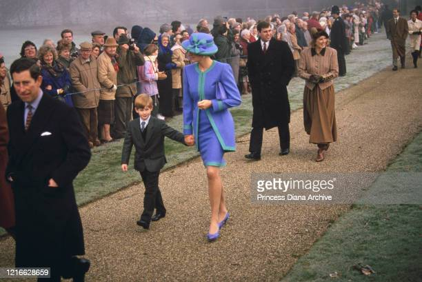British royals Prince Charles, Prince Harry, Diana, Princess of Wales , wearing a blue and turquoise suit by Catherine Walker, with a matching hat,...