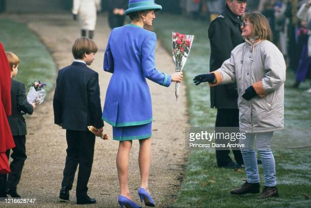 British royals Prince Harry Prince William and their mother Diana Princess of Wales wearing a blue and turquoise suit by Catherine Walker with a...