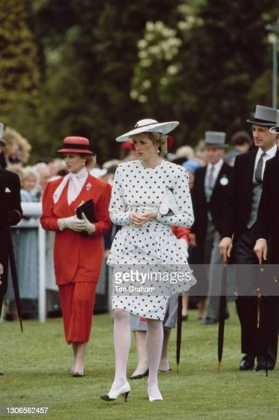 British Royals Princess Alexandra, wearing a red suit, and Diana, Princess of Wales , wearing a dress by Victor Edelstein and hat by Frederick Fox,...