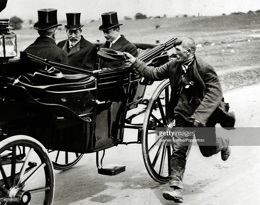 British Royalty pic: 1925. HM.King George V, centre, with Henry, Duke of Gloucester travelling by carraige at Epsom races, receive a somewhat unwanted request from a gypsy man requesting money, as he runs alongside offering his cap. King George V (1865-1 : News Photo