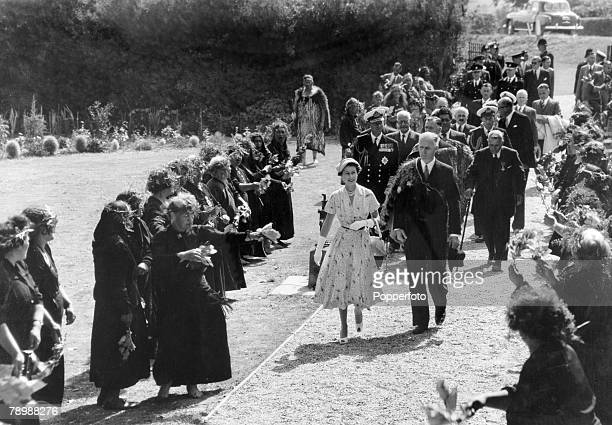 1954 New Zealand HM Queen Elizabeth with the Duke of Edinburgh behind pictured arriving at Waitangi during the Royal Tour passing an avenue of Maori...