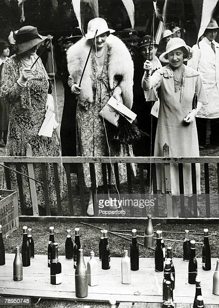 "July 1933, HRH,The Duchess of York, right, pictured ""fishing"" for champagne at a garden partyat Portman House, London, in aid of the Princess..."