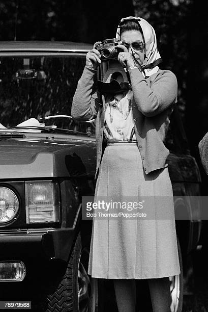 British Royalty Royal Windsor Horse Show England May 1982 Queen Elizabeth II wearing a headscarf prepares to take a photograph with her Leica camera