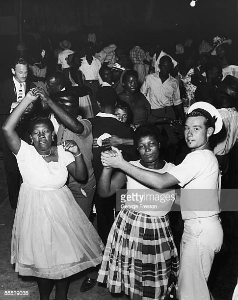 A British sailor joins Jamaicans at a dance in Kingston to celebrate after independence was granted to Jamaica 6th August 1962 The island was...
