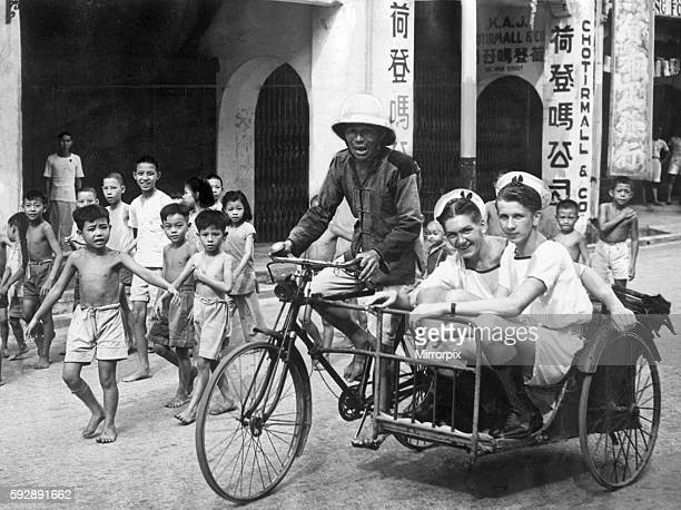 British sailors of the Royal Navy on shore leave in Singapore are transported by an elderly local man in his rickshaw as children look on at the end...