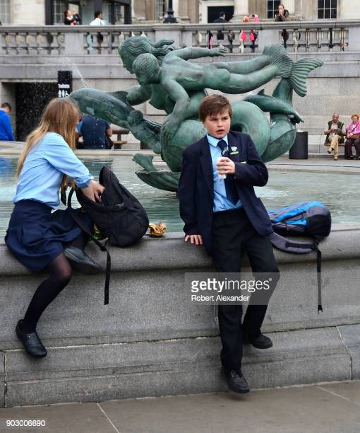 British school students on a field trip eat their lunches in front of the National Gallery in London, England.
