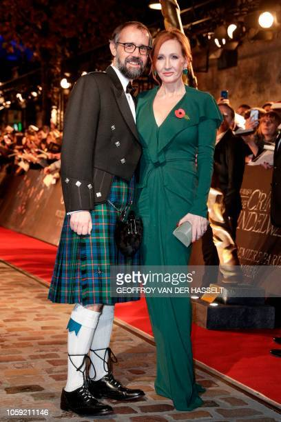 British screenplay writer J K Rowling poses with her husband Neil Murray for a photograph as they arrive for the premier of the fantasy film...