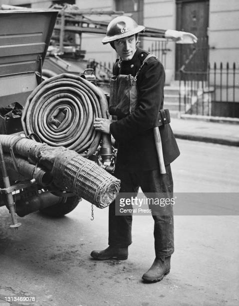 British sculptor and artist Loris Rey working as a firefighter for the Auxiliary Fire Service on 12th March 1941 in London, England. Rey was also the...