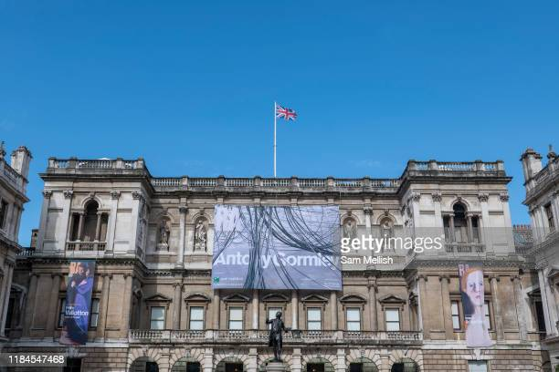 British sculptor Antony Gormley exhibition promotional display hanging from the exterior building of the Royal Academy of Arts at Burlington House on...