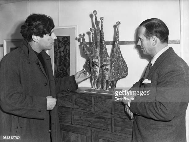 British sculptor Kenneth Armitage discusses his work 'People in the Wind' with artist Graham Sutherland at a preview of works destined for the Venice...
