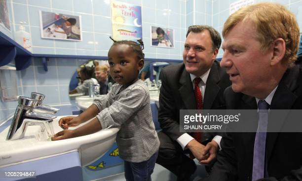 British Secretary for Education and Children Ed Balls and Chief Medical Officer Sir Liam Donaldson watch a child wash their hands during a visit to...