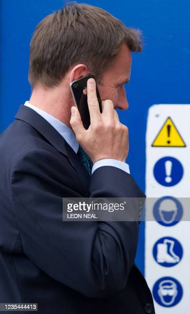 British Secretary of State for Culture, Olympics, Media and Sport, Jeremy Hunt, talks on his mobile as he leaves his office to make a statement in...