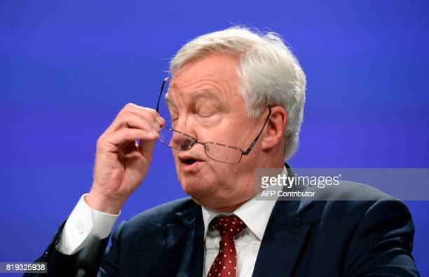 British Secretary of State for Exiting the European Union David Davis adjusts his glasses as he addresses media representatives during a press...