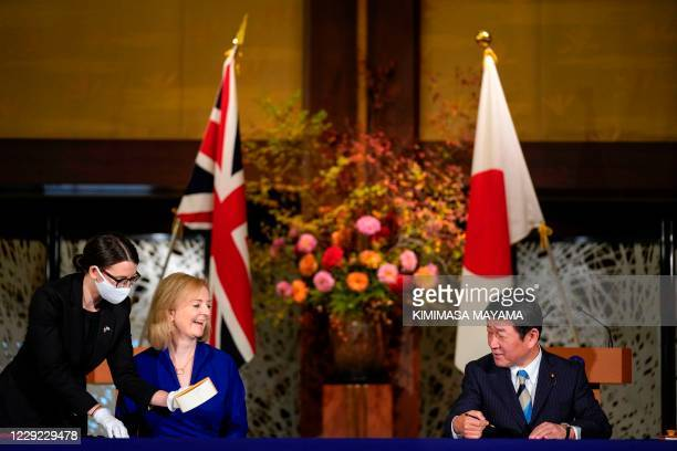 British Secretary of State for International Trade Elizabeth Truss and Japanese Foreign Minister Toshimitsu Motegi take part in a signing ceremony...