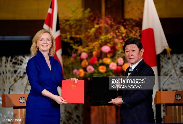 British Secretary of State for International Trade Elizabeth Truss and Japanese Foreign Minister Toshimitsu Motegi exchange documents during a...