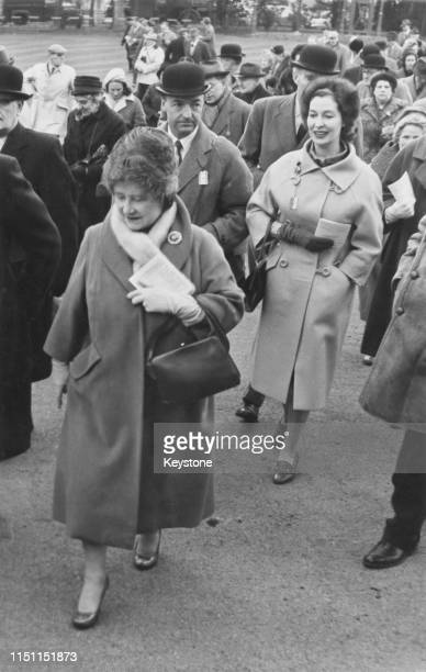 British Secretary of State for War John Profumo and his wife actress Valerie Hobson behind Queen Elizabeth The Queen Mother in the parade ring at...